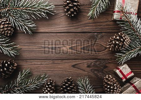 Brown wood background. Fir branches, decorative cones. Message space for Christmas and New Year. Gifts for xmas. Greeting card. Xmas and Happy New Year composition. Flat lay, top view