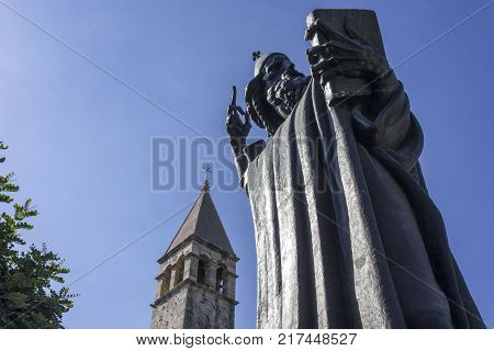 SPLIT, CROATIA - AUGUST 11 2017: Looking up at the statue of the bishop Gregory of the Nin in Split with the Bell Tower of St. Arnir in the background