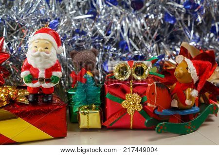 Santa Claus figurine with gifts and blue and silvery tinsel as decoration for Christmas