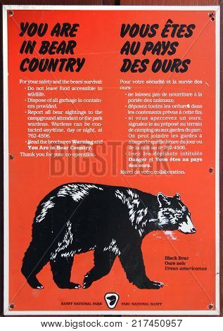 BANFF CANADA - July 8 2011: Bear warning sign posted at Banff National Park campground in Alberta Canada reminding visitors of black bears in the area while hiking or camping.