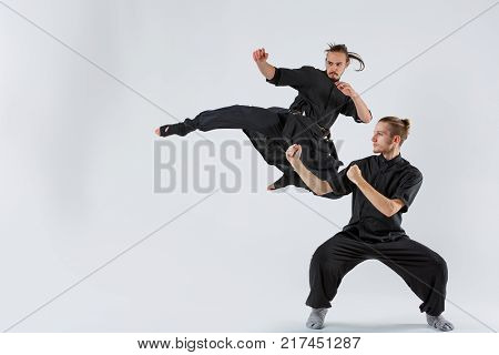 Two ninjas are young, experienced in black forms. One stands in the fighting stance and the second in the jump with the foot forward on a gray background