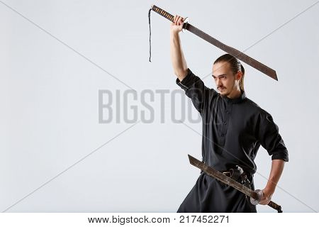 A young ninja man in black uniform holds two swords in parallel. One above the head of the other below in the hand on a gray background