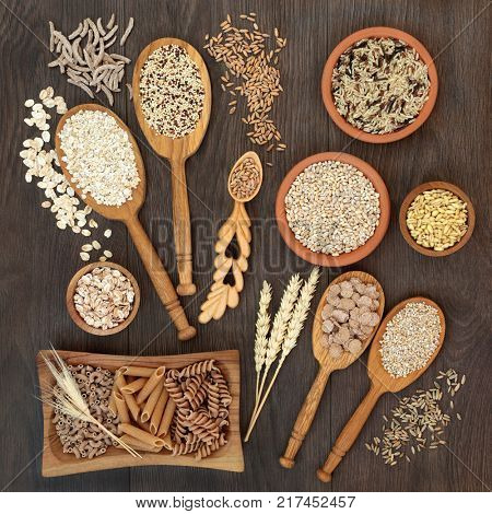 High fiber health food of whole wheat pasta, cereal and grains in bowls and spoons on rustic oak background.