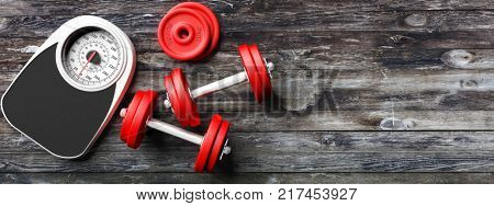 Bathroom scale, dumbbells on the left side of a wooden floor background. Copyspace. 3d illustration