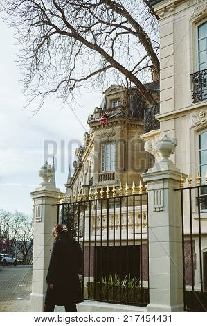STRASBOURG FRANCE - DEC 9 2016: Russian woman walking near the Russian Embassy Consulate building protected by luxury fence in Strasbourg Alsace