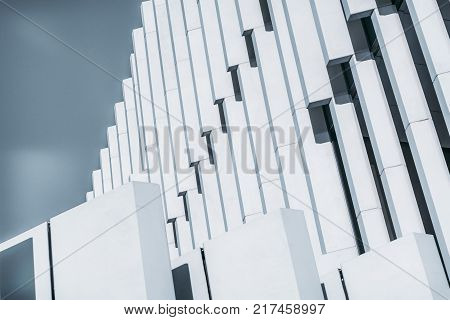 Side view of abstract white contemporary building facade with thick concrete vertical striped blocks; close-up view of outdoor bright exterior of modern house with sky in background