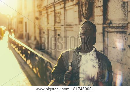 Black pensive undergraduate guy in denim jacket is standing on a street and looking up; handsome African male student nerd outdoor on a street of Lisbon city on his way to college or university