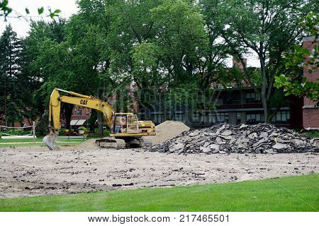 JOLIET, ILLINOIS / UNITED STATES - JULY 26, 2017: A Cat 320 hydraulic excavator digs up a parking lot at the University of Saint Francis.