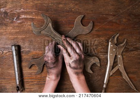 Female repairer. Woman hand holding a spanner and other tools lay on a wooden background. Feminism and empowerment concept