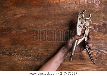 Female plumber. Woman dirty hands holding a wrench on a wooden background. Hardwork for a girl