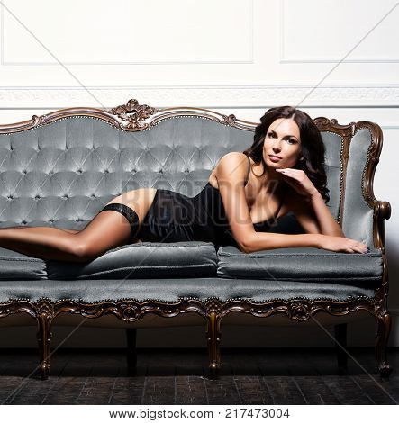 Sexy, voluptuous woman in erotic lingerie and stockings posing on a grey sofa.