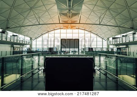 Business travel help desk in the main terminal for traveler or passenger in international airport for travel with blank board for text. Airport interior for background.