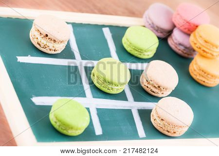 Tic-tac-toe with macarons on table close up