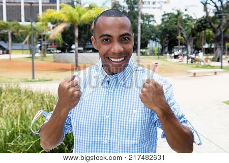 Successful cheering african american man outdoors in the summer in the city