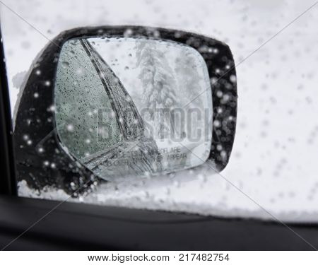 Closeup of car side mirror with snowflakes and trees in snow. Heavy snowfall.