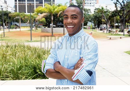 Laughing african american man outdoors in the summer in the city