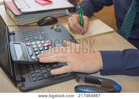 Hands of accountant with calculator and pen. Accounting background. Businessman using a calculator to calculate the numbers. Man hand with calculator at workplace office