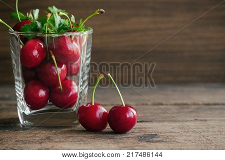 Fresh red cherries in clear glass put on wooden table. Cherry in side view with copy space for background. Cherry have high vitamin C and have sweet and sour taste. Fruit background and wallpaper concept. Cherry is delicious and healthy fruit.