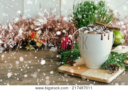 Hot chocolate in white cup topping with marshmallow and chocolate sauce. Homemade hot chocolate or cacoa on wood table with copy space in Christmas theme and snowfall background. Concept of Christmas drink. Delicious hot chocolate for Christmas party.