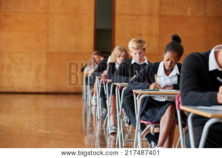 Teenage Students In Uniform Sitting Examination In School Hall