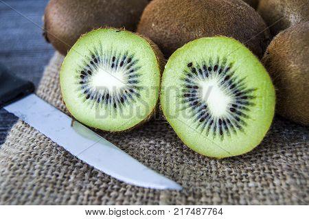 kiwi fruit, two pieces of kiwi with knife, kiwi standing on wooden floor