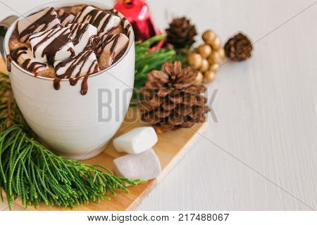 Hot chocolate in white cup top with marshmallow and chocolate sauce. Homemade hot chocolate or cacoa on wood table in top view copy space with Christmas theme background. Concept to present Christmas drink. Delicious hot chocolate ready to served.