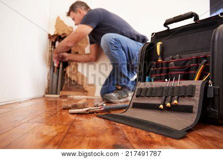 Middle aged man repairing burst pipe,plumbing, focus on foreground poster