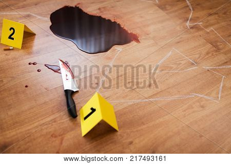 murder, kill and forensic evidence concept - chalk outline of body and knife in blood lying on floor at crime scene (staged photo)