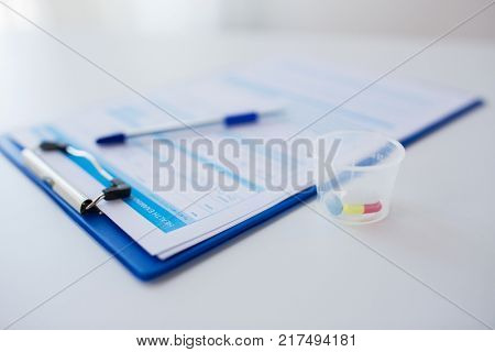 medicine and healthcare concept - clipboard with report and drugs in medical cup