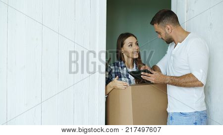 Young woman deliver cardboard box to customer at home. Man writing digital signature on tablet computer for receiving parcel