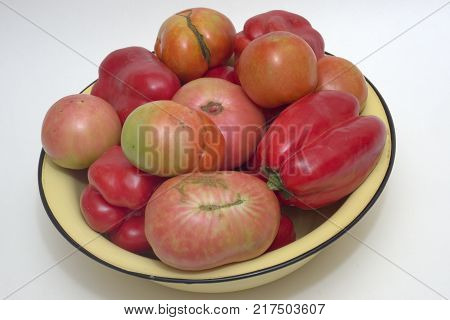 yellow basin overflowed with red and pink fresh tomatoes and red sweet peppers