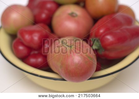yellow basin with black rim, overfull with red and pink fresh tomatoes and red sweet peppers. Closeup
