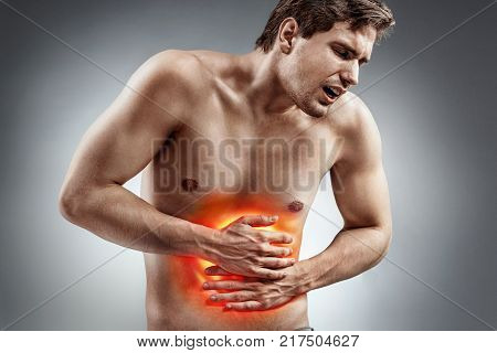 Abdominal pain. Photo of man with naked torso experience irritable bowel syndrome on grey background. Medical concept.