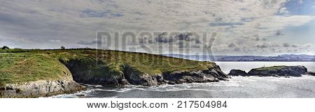 Rocky cliff on the Atlantic coast of Galicia with La Coruna in the background the calm sea and a cloudy sky