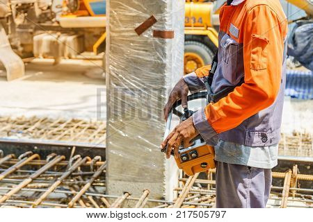 builder worker controlling trailer-mounted boom concrete pump on metal rods reinforcement of concrete casting formwork
