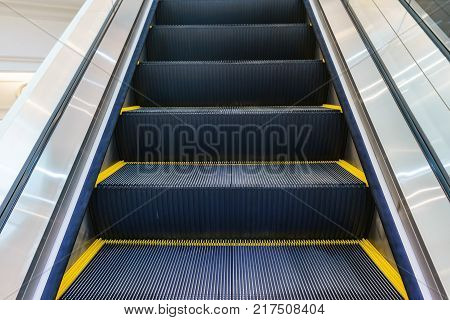 Escalator in Community Mall Shopping Center. Moving up staircase. electric escalator. Close up to escalators. Close up floor platform. yellow bands. metal line steel. yellow gray steel line.