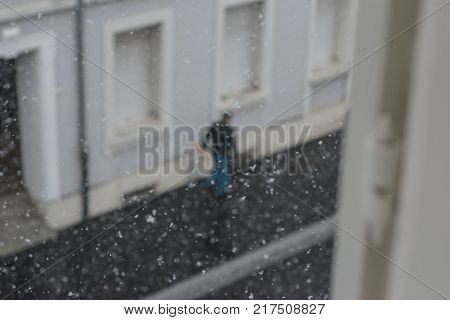 man walking down a road during a snowy day