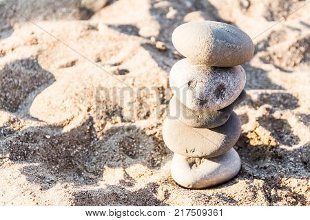 Stones stacked by a turret on the seashore, similar to a creature with eyes. Light.