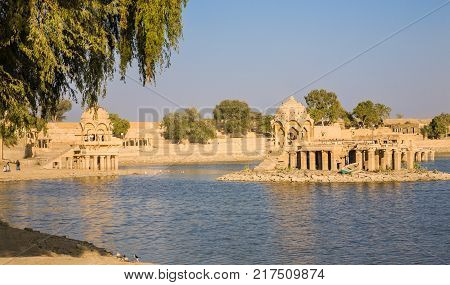 Jaisalmer India - 2015 January 5 : The artificial Gadsisar Lake with temples and ghats near the desert town of Jaisalmer in the Rajasthan region of northern India
