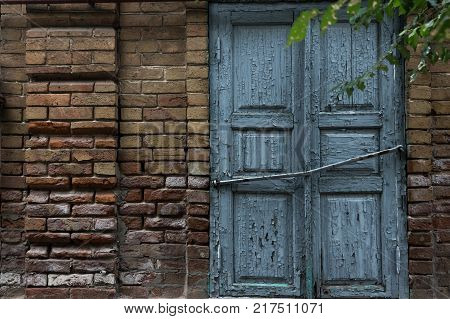 The old window is covered with blue shutters on a vintage brick wall.