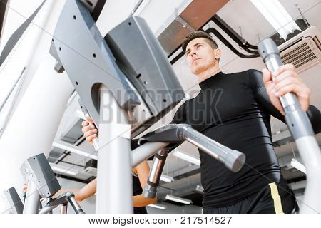 Young fit male working out on an elliptical trainer in a gym