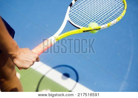 Closeup of a player holding the racquet and preparing for the serv at the baseline