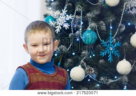 little boy decorates a Christmas tree beautiful Christmas decorations
