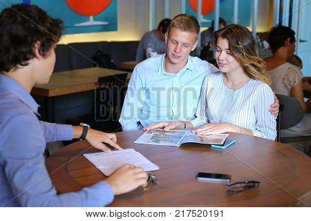 Young business rich couple buy an apartment, property, house, apartment, enter into a contract with a realtor. Signs an agreement with the seller, Leaf catalog pages