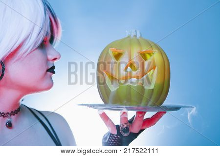 close up of a sexy woman with a scary halloween pumpkin with cold iced smoke