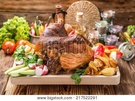 Roasted sliced pork ham and roast vegetables on dark rustic background, top view