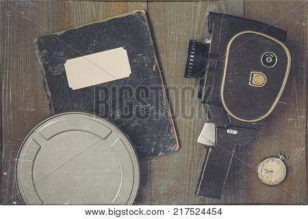 An old movie camera a watch a metal box with a film and a black shabby notebook with a script lay on a wooden table. A stylized photo.