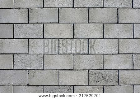 Flat wall of light gray rectangular concrete blocks. Large blocks and even dark seams. Blocks are not smooth textured and not of the same type.