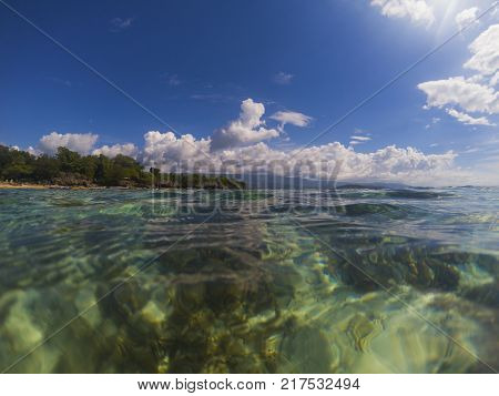 Sea water and sunny blue sky double landscape photo. Tropical seaside banner. Above and below waterline. Natural scene with ocean water surface. Still sea ripples on clean seawater. Sunny seashore