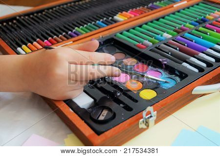 Child painting a picture. A little girl's hand holding a paintbrush with an art supplies kit featuring paint and markers. Arts and crafts concept. Traditional play concept.